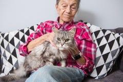 Den mycket gamla höga Caucasian farmodern med grått hår och djupa skrynklor sitter hemma på soffan i jeans och a arkivfoton