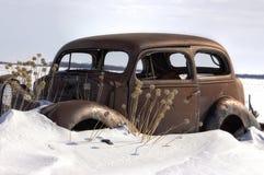 Den mycket gamla rostade tappningbilen klibbade i snö Arkivbilder
