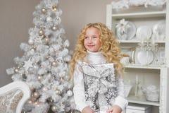Den mycket glade lilla flickan rymmer en gåvaask på händer och ser upp i jul Arkivbilder