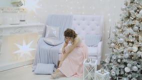 Den mycket härliga flickan dricker champagne och sitter på soffan i det nya årets dekor arkivfilmer