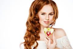 Den mycket härliga flickan med ursnyggt rött hår som rymmer en orkidé, är arkivbilder