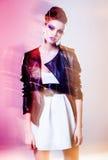 Den mycket härliga kvinnan som poserar i ett läderomslag - vinka ljus och färger Arkivbilder