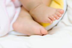 Den mycket lilla foten av den gulliga asiatet behandla som ett barn att sova på säng Royaltyfri Bild