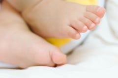 Den mycket lilla foten av den gulliga asiatet behandla som ett barn att sova på säng Royaltyfri Fotografi
