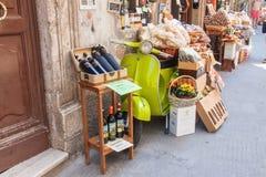 Den mycket lilla marknaden ställer ut gods på en Iconic italiensk sparkcykel i Pitigliano Royaltyfria Bilder