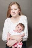 Den mycket unga flickan med nyfött behandla som ett barn royaltyfri foto