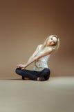Den mycket uttrycksfulla blonda flickan i en vit sönderriven överkant och jeans sitter på Arkivfoton