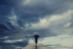 Den mystiska kvinnan med paraplyet korsar en bro till den overkliga sikten av himlen royaltyfri fotografi