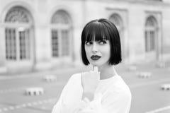 Den mystiska kvinnlign har idé Guppar den trendiga damen för flickan med utomhus- stads- arkitekturbakgrund för frisyren Kvinna royaltyfri bild