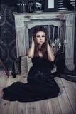 Den mystiska sammanträdeunga flickan i svart haloween klänningen Royaltyfri Foto