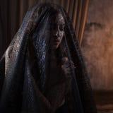 Den mystiska ståenden av den härliga kvinnan i svart snör åt skyler Royaltyfria Foton