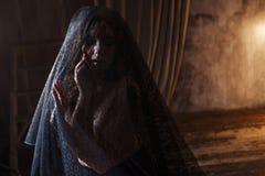 Den mystiska ståenden av den härliga kvinnan i svart snör åt skyler Royaltyfri Foto