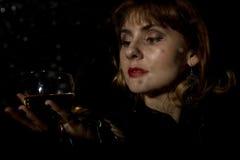 Den mystiska unga kvinnan med ett exponeringsglas av vin som poserar bak genomskinligt exponeringsglas som täckas av vatten, tapp Arkivfoton