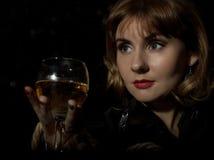 Den mystiska unga kvinnan med ett exponeringsglas av vin som poserar bak genomskinligt exponeringsglas som täckas av vatten, tapp Royaltyfri Bild