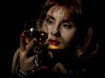 Den mystiska unga kvinnan med ett exponeringsglas av vin som poserar bak genomskinligt exponeringsglas som täckas av vatten, tapp Arkivbilder