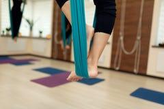 Den nära övre kvinnan lägger benen på ryggen staget i hängmattan som gör flugayoga som sträcker övningar i idrottshall Passform-  arkivbilder