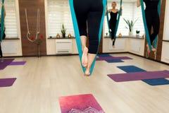 Den nära övre kvinnan lägger benen på ryggen staget i hängmattan som gör flugayoga som sträcker övningar i idrottshall Passform-  arkivbild