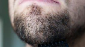 Den nära övre mannen rakar skägget på framsida med den svarta rakkniven Den orakade mannen använder rakkniven för att raka hakan arkivfilmer
