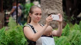 Den nära övre modermamman med behandla som ett barn i resor för en rem runt om ön och tar bilder på en smart telefon för socialt arkivfilmer