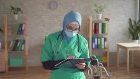 Den nära övre ståenden av en kvinnlig doktor är en muslim kvinna med en mapp lager videofilmer