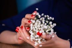 Den nära övre ståenden av flickor manicured händer som rymmer inskränkt djup för liten gullig blommabukett av fältet arkivfoto
