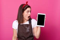 Den nära övre ståenden av kvinnaställningar över rosa bakgrund, rymmer den smarta telefonen, ser åt sidan på hennes grej Mörkt gj arkivbild
