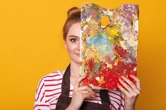 Den nära övre ståenden av målaren för den unga kvinnan mot den gula studioväggen, drar bilden, damen som bär den tillfälliga rand arkivbilder