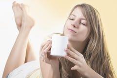 Kuper den unga kvinnan för naturlig skönhet som har morgon, av kaffe eller tea Royaltyfri Bild