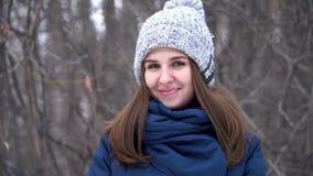 Den nära övre ståenden av den stilfulla unga härliga kvinnan ler i en vinter parkerar över snöig bakgrund härligt model barn lager videofilmer