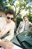 Affärsmän som möter runt om bilen. Royaltyfri Fotografi