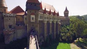 Den nära flyg- sikten av en medeltida slott med bron som omges av gräsplan, parkerar stock video