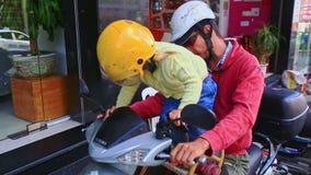Den nära lilla blonda flickan i hjälmplatser på motorcykeln shoppar förbi arkivfilmer