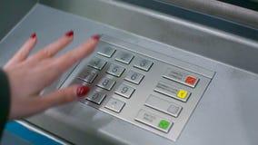 Den nära siktsflickahanden trycker på knappar på det gråa tangentbordet för ATM arkivfilmer