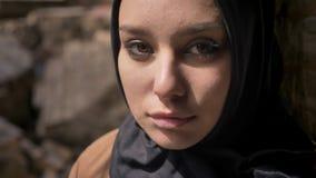 Den nära ståenden av den unga muslimkvinnan i svart hijab som ser kameran, stående near tegelstenvägg, härligt charma, synar