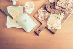 Den näringsrika frukosten, ingredienser för framställning skjuter in med salami, smör och ost, yoghurt på en träbästa sikt för ta arkivbild