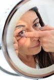 Den närsynta kvinnan sätter en kontaktlins Arkivbilder