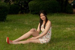 Den nätt asiatiska kvinnan poserar av sammanträde på en lawn i parkera. fotografering för bildbyråer
