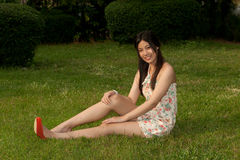 Den nätt asiatiska kvinnan poserar av sammanträde på en lawn i parkera. arkivfoto