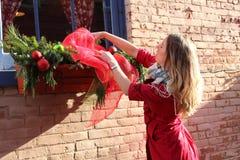 Den nätt blondinen i rött klä upp fönster boxas Arkivbilder