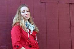 Den nätt blondinen i rött klår upp mot den röda ladugårdväggen Royaltyfria Bilder