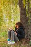 den nätt bokflickan läser den tonårs- treen under Arkivbilder