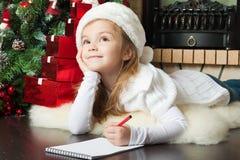 Den nätt flickan i den Santa hatten skriver bokstaven till Santa Arkivfoton