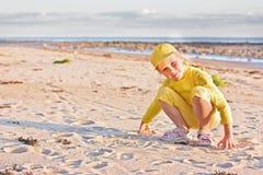 Den nätt flickan i en guling klumpa ihop sig locket Arkivbilder