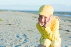Den nätt flickan i en guling klumpa ihop sig locket Arkivfoton