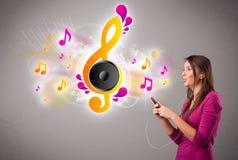 Den nätt flickan som sjunger och lyssnar till musik med musikal, noterar arkivfoto