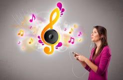 Den nätt flickan som sjunger och lyssnar till musik med musikal, noterar royaltyfri fotografi