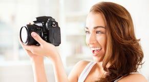 Den nätt kvinnan är en proffessionalfotograf med dslrkameran Royaltyfria Bilder