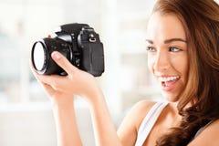 Den nätt kvinnan är en proffessionalfotograf med dslrkameran Arkivfoto