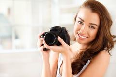 Den nätt kvinnan är en proffessionalfotograf med dslrkameran Arkivbild