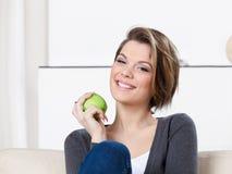 Den nätt kvinnan äter ett grönt äpple Royaltyfri Fotografi